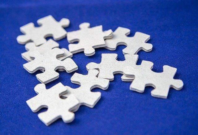 Piezas de puzzle blancas sobre fondo azul para indicar que el diseño lingüístico se construye