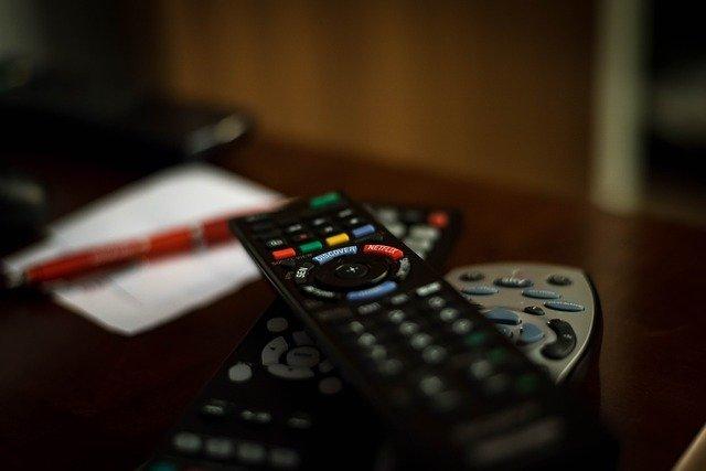 Varios mandos de televisión con una papel y bolígrafo para anotar de fondo para ilustrar este blog de idiomas en el cine y series