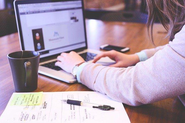 Mujer escribiendo en computadora sobre mesa en la que hay teléfono, taza y papel con anotaciones