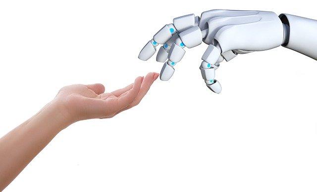 Mano humana acercándose a mano robot