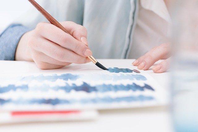 Mujer pinta con un pincel lo que parecen ondas de sonido de diferentes colores