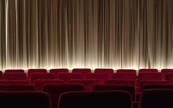 Cual capas o estratos lingüísticos, la imagen tiene cinco filas de butacas con una cortina de cine o teatro con muchos pliegues